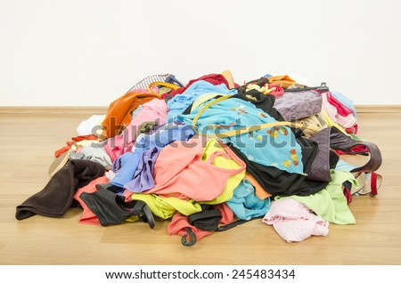 Close up on a big pile of clothes and accessories thrown on the ground. Untidy cluttered wardrobe with colorful clothes and accessories. - stock photo