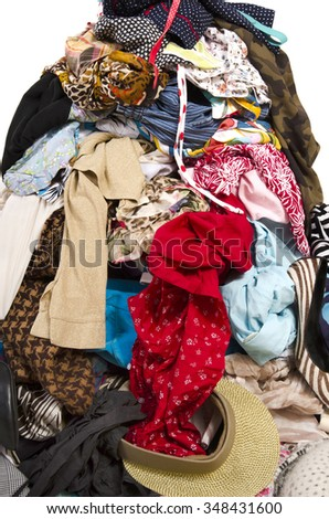 Close up on a big pile of clothes and accessories thrown on the ground. Untidy cluttered wardrobe with colorful clothes and accessories.