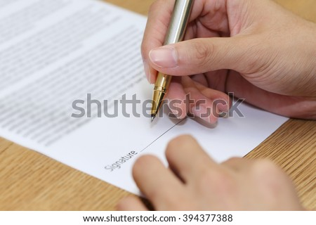 close-up on a businessman hand signing a contract paper - stock photo