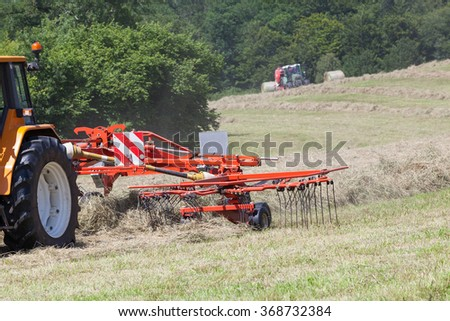 Close up on a farmer using a rotary rake to turn dried grass for hay and fodder for livestock with some motion blur to the tines. Baler baling the crop in the background.  - stock photo