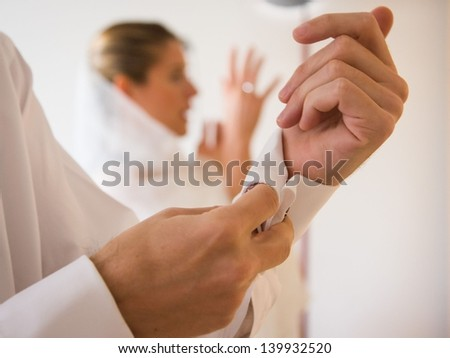 Close-up on a groom's hands in the foreground as he is bottoning the shirt's sleeve before the wedding and in the background the wife is preparing