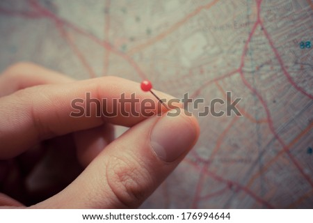 Close up on a hand placing a pin on a map - stock photo