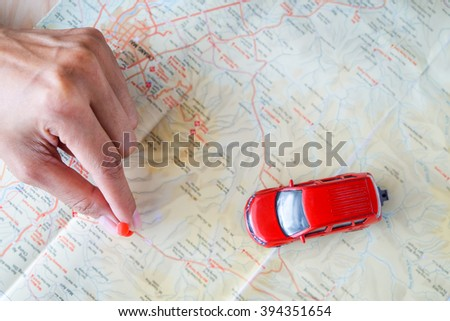 close up on a hand placing a pin on a map and car toy mark where to go - stock photo