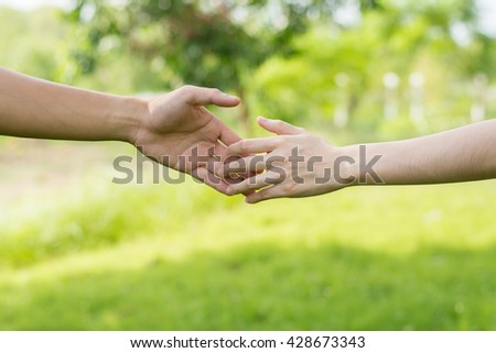 Close up on a man and a woman holding hands at green background.