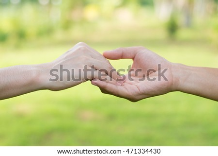 Close up on a man and a woman holding hands at green background,Hand help and hope concept,helping hand