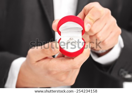 Close-up on a man holding an engagement ring with the focus on the ring - stock photo