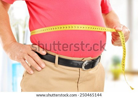 Close-up on a man measuring his belly at home - stock photo