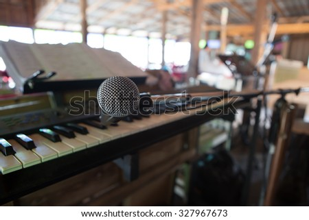 Close up on a microphone during recording session with a singer, piano in the background