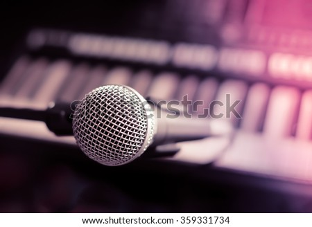 Close up on a microphone during recording session with a singer, piano in the background, music studio, light leak style