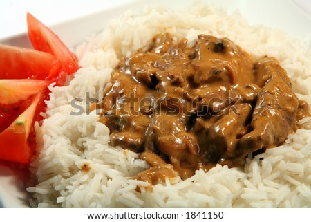 Close-up on a plate of beef and mushroom stroganoff, on basmati rice garnished with tomato. - stock photo
