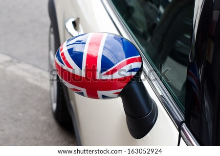 Close up on a side mirror of a car with the UK flag on it. Patriotic driver. England flag. - stock photo