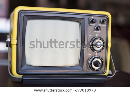 Close up on a vintage portable television, background is blurred. Monitor is off.