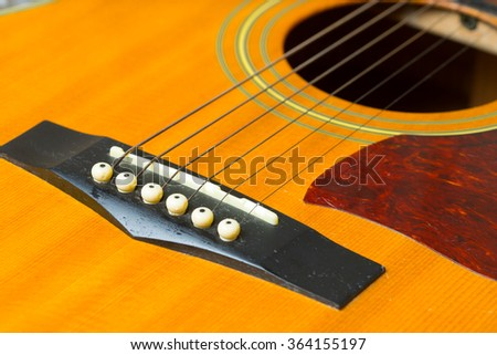 Close up on a well used wooden guitar