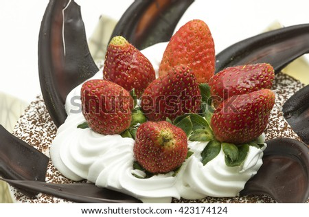 Close up on a whole round cake with topping of fresh strawberry fruits on white cream, sprinkle with cocoa powder and decorated with chocolate shards and sheets - stock photo