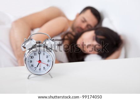 Close-up on alarm clock and lovely young couple on background - stock photo