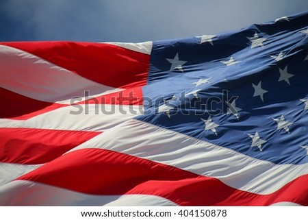 Close Up on American Flag Stars and Stripes Waving against Cloudy Sky in Afternoon Sun
