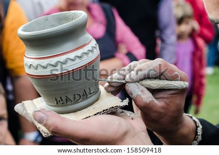 Close-up on artist hands personalizing a clay jug by writing the name of a person.