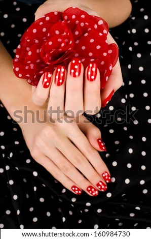 Close up on beautiful female hand with cute red manicure with white dots. Black dotted background. - stock photo