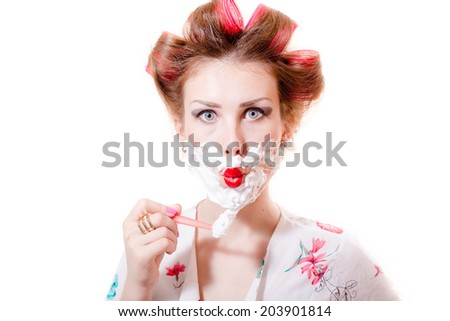 close up on beautiful young pinup lady having fun shaving face looking at camera isolated on white or light copy space background portrait picture - stock photo