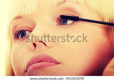 Close up on beautiful young woman doing make up on eyelashes. - stock photo