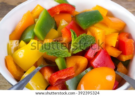 Close up on bell pepper salad decorated with mint in bowl on wooden table
