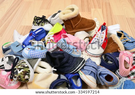 Close up on big pile of baby shoes. Untidy stack of boy and girl toddler shoes thrown on the ground. - stock photo