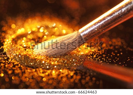 Close-up on brush and shining powder. Very shallow focus on tip of the brush. - stock photo