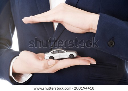 Close up on car toy model on woman's hand over her belly and formal clothes. - stock photo