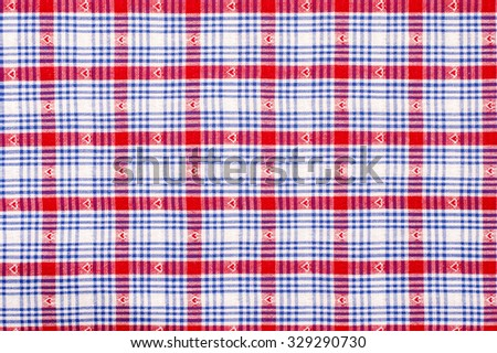 Close up on checkered tablecloth fabric. Red and blue with hearts tartan square pattern as background. - stock photo
