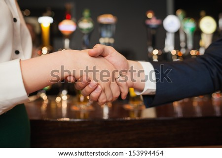 Close up on colleagues shaking hands during meeting in a classy bar - stock photo