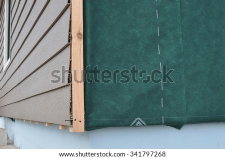 Close up on corner  thermal insulation of a house wall on a building site. Construction or repair of the rural house,plastic siding, fixing facade, membrane,  insulation house wall. - stock photo