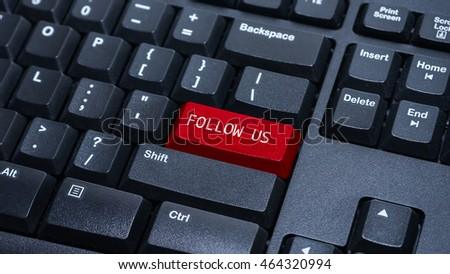 Close up on customized computer enter button on keyboard with a word follow us.