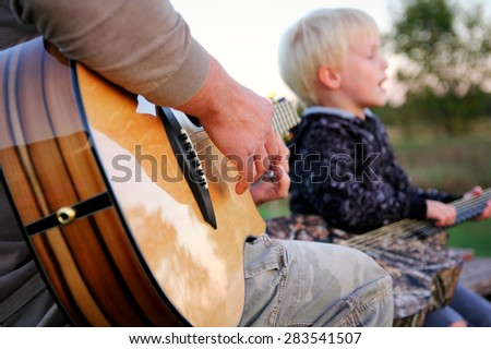 Close up on exotic wood bottom of a guitar being played by a father as his son sings in the background.