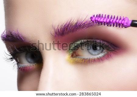 Close up on eyes , making colorful eyeshadows and eyeliner tutorial - stock photo
