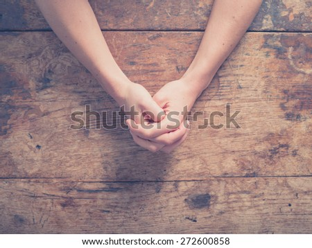 Close up on female hands folded in prayer at a wooden table - stock photo