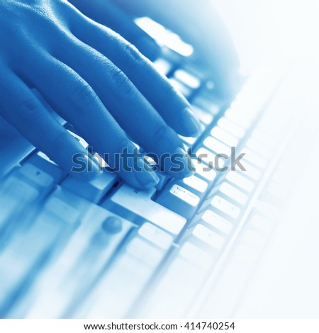 Close up on fingers texting on a computer keyboard - stock photo