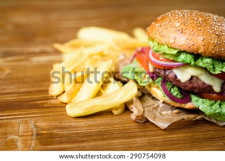 Close up on fresh made hamburger with tomato, lettuce, onion and a pile of fries.