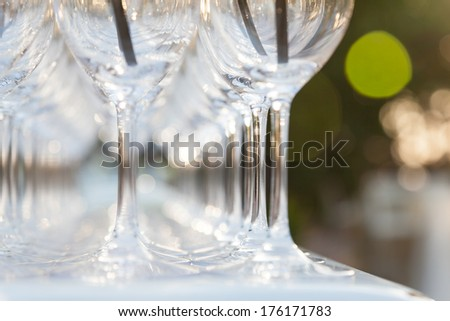 Close-up on glasses on the celebration table with guests on the background