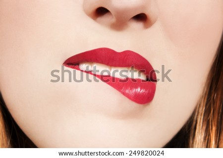 Close up on gorgeous model biting her red lips  - stock photo