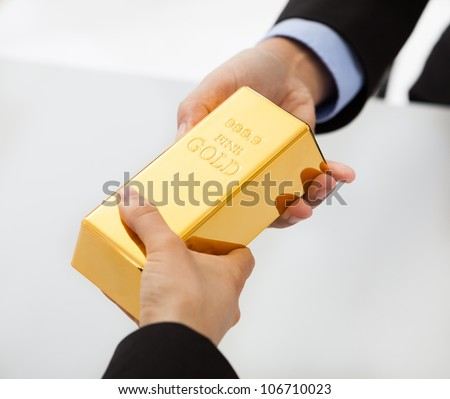 Close-up on hand of business people exchanging golden bar