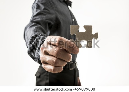 Close up on hand of unidentifiable business man holding puzzle piece over neutral background for concept about solutions to problems.
