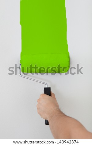Close-up On Hand Painting Wall In Green - stock photo