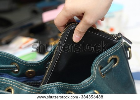 close-up on  hand pickpocketing a purse in a woman bag - stock photo