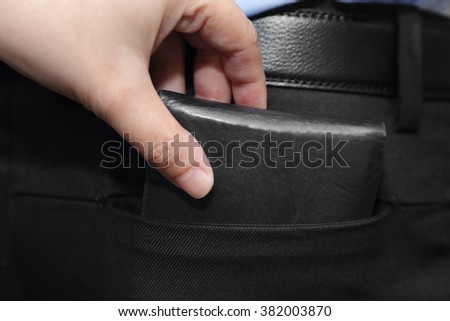 close-up on  hand pickpocketing wallet of a businessman - stock photo