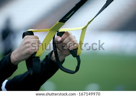 Close up on hands doing suspension training - stock photo