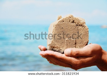 Close up on hands holding Home made from sand. House on seashore. Summer holiday, vacation, postcard, background.  Real estate investment concept - stock photo