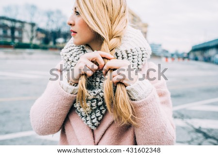Close up on hands of young beautiful caucasian blonde woman weaving her hair on a braid - hair styling, care concept - stock photo