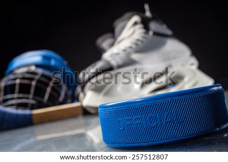 Close-up on hockey puck and hockey equipment in background.
