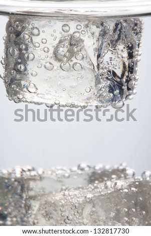 Close up on ice cube into a glass of sparkling water - stock photo