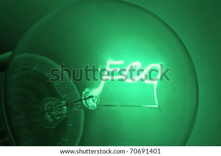 "Close up on illuminated green light bulb filament spelling the word ""Eco"". - stock photo"